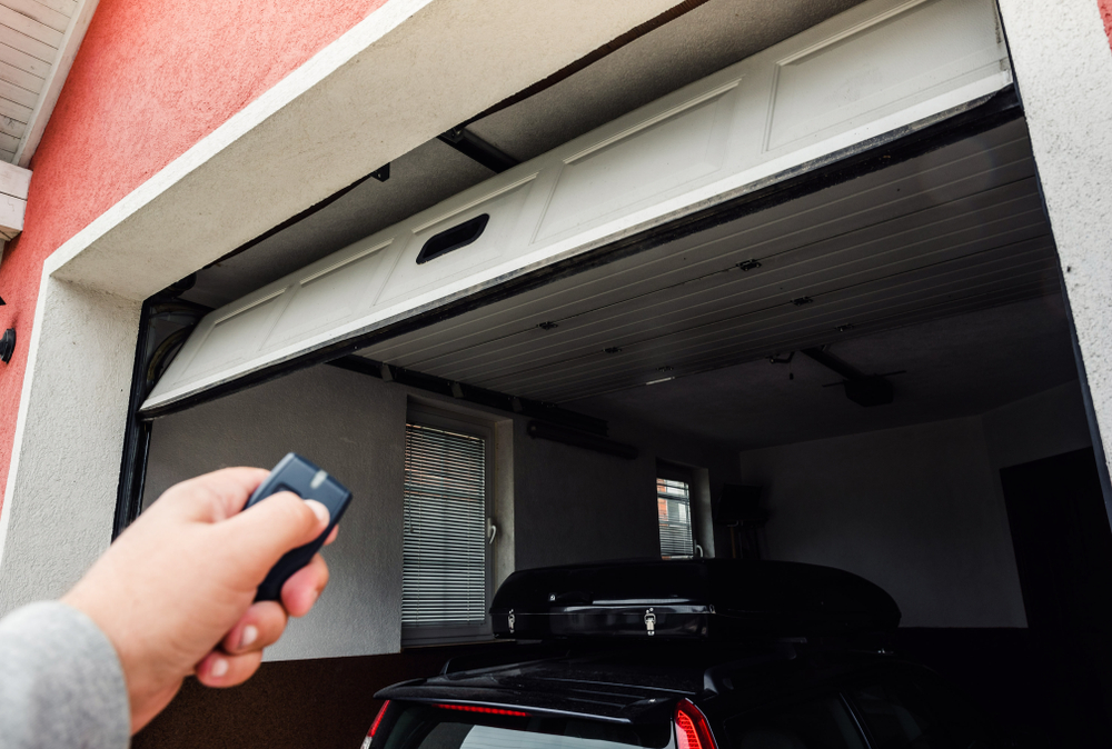 A man opening garage door with help of automated remote control