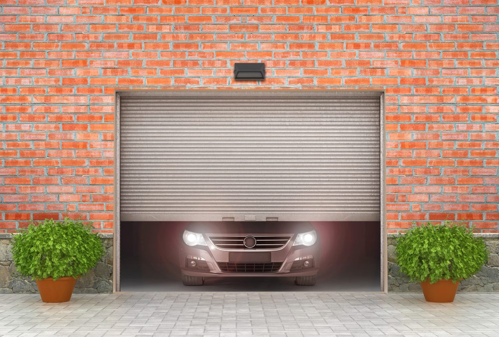 Half open metal garage door with slightly visible car front