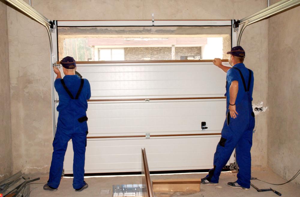 Two technicians insulate a garage door.