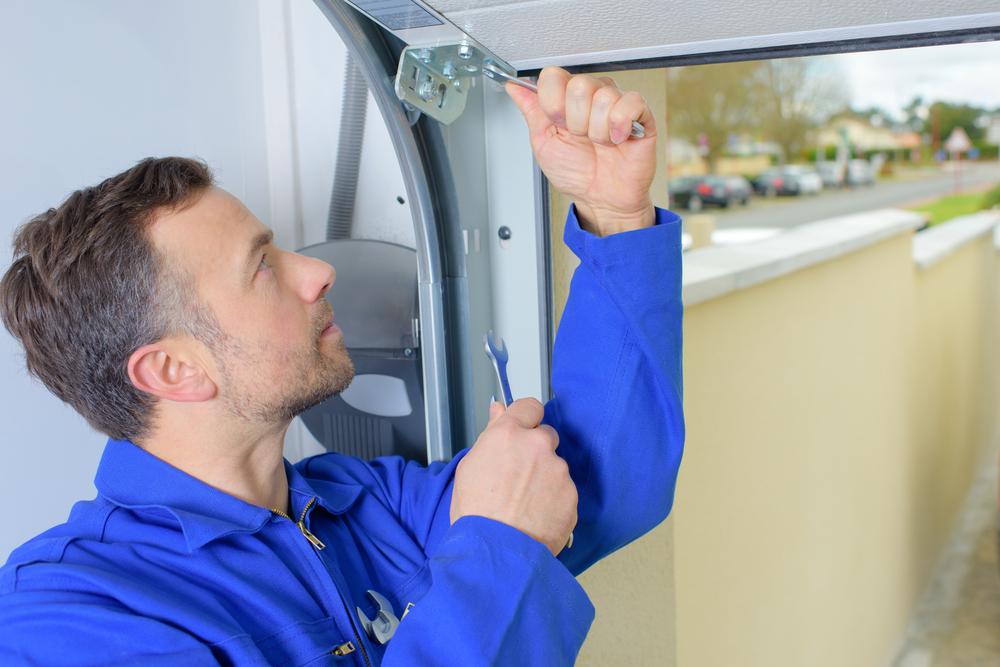 A technician servicing a garage door