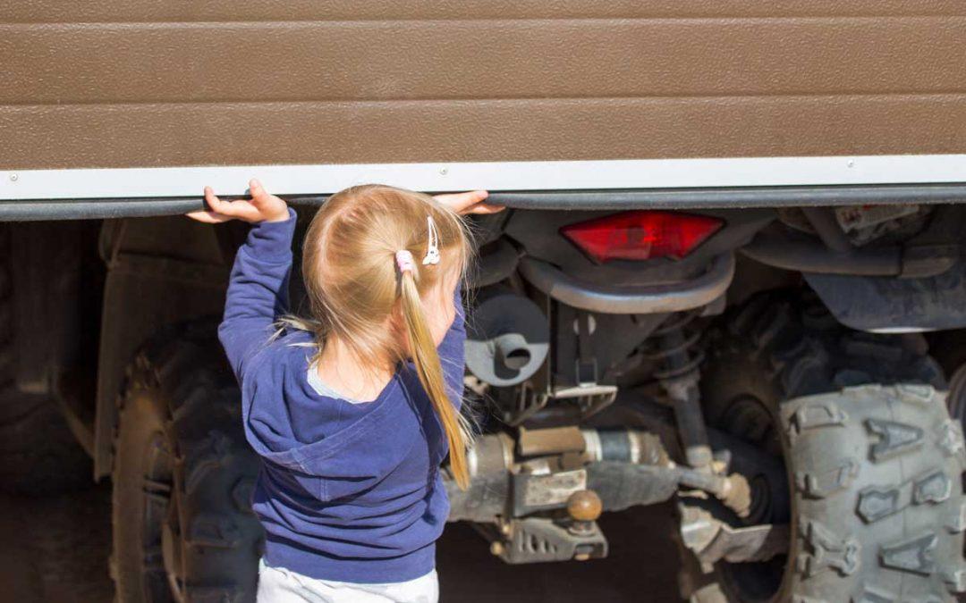 Little girl opening garage door where ATV stands. Back view.
