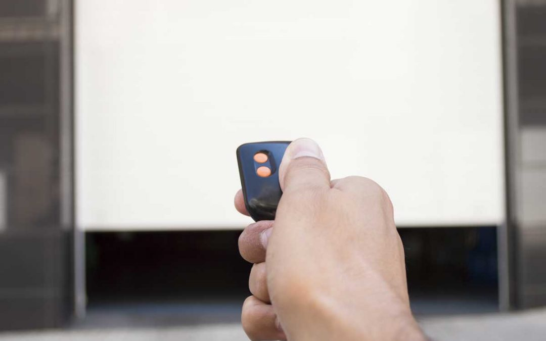 hand pressing a remote control with the door open